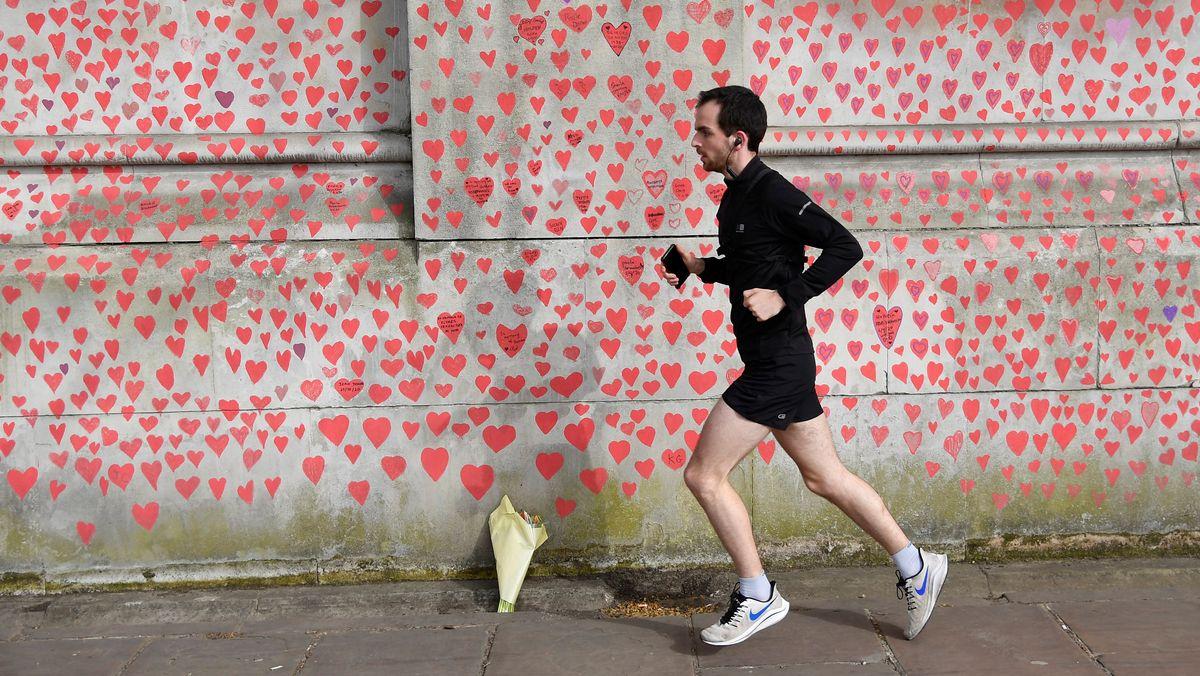 Einsamer Jogger in London vor einer Wand mit Herzen, die Angehörige und Freiwillige zum Gedenken an die britischen Coronatoten gemalt haben.