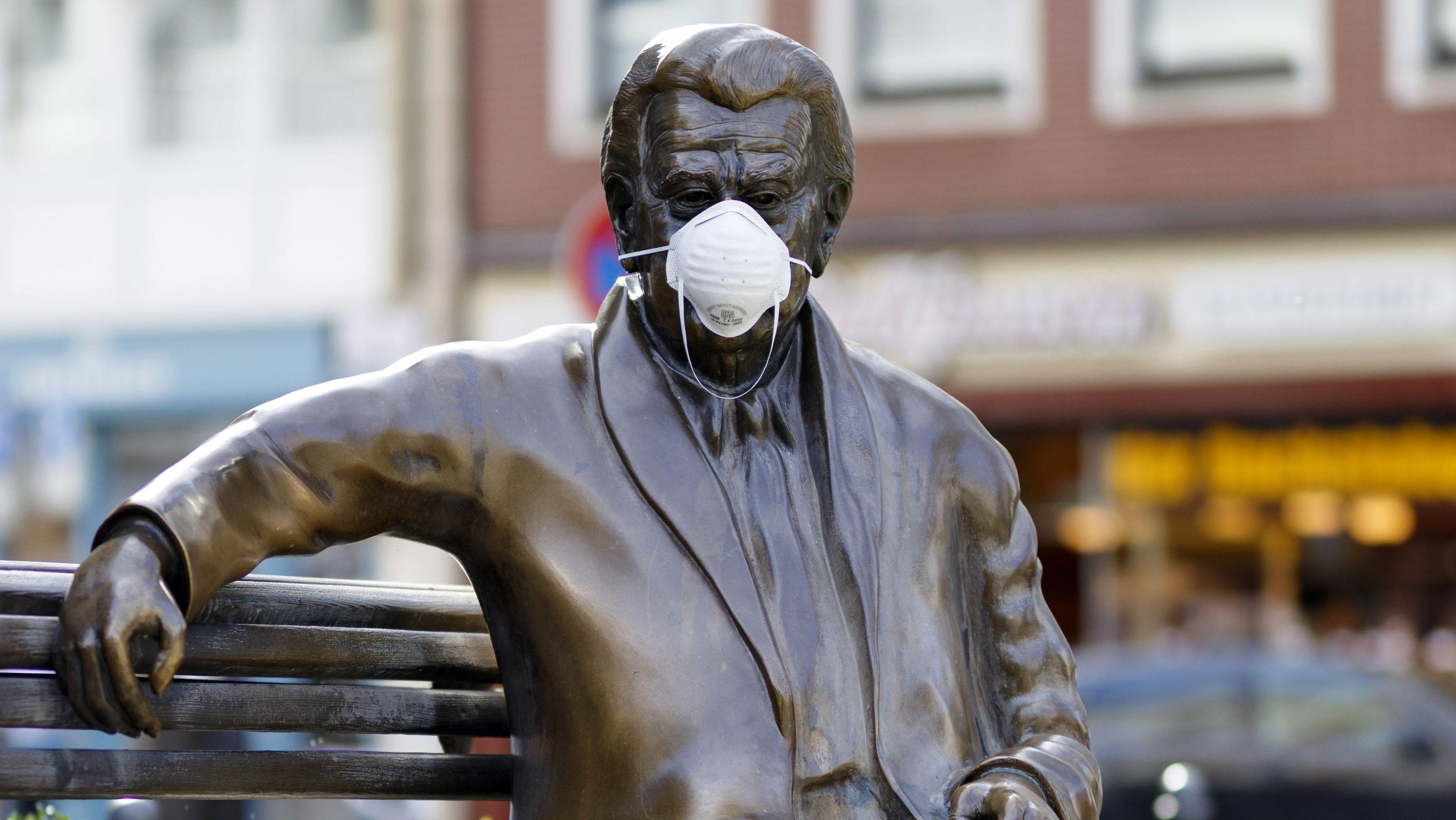 Jemand hat eine Bronzestatue mit einer Atemmaske ausgestattet.