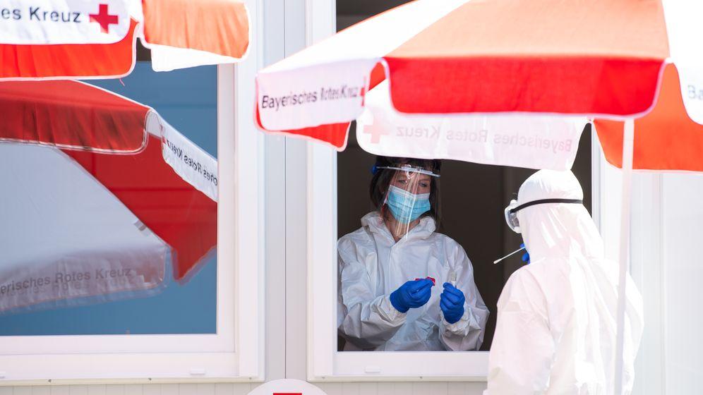 Mitarbeiter vom Bayerischen Roten Kreuz stehen in einem Corona-Testzentrum an der A8 an der Rastanlage Hochfelln-Nord.  | Bild:dpa / Sven Hoppe