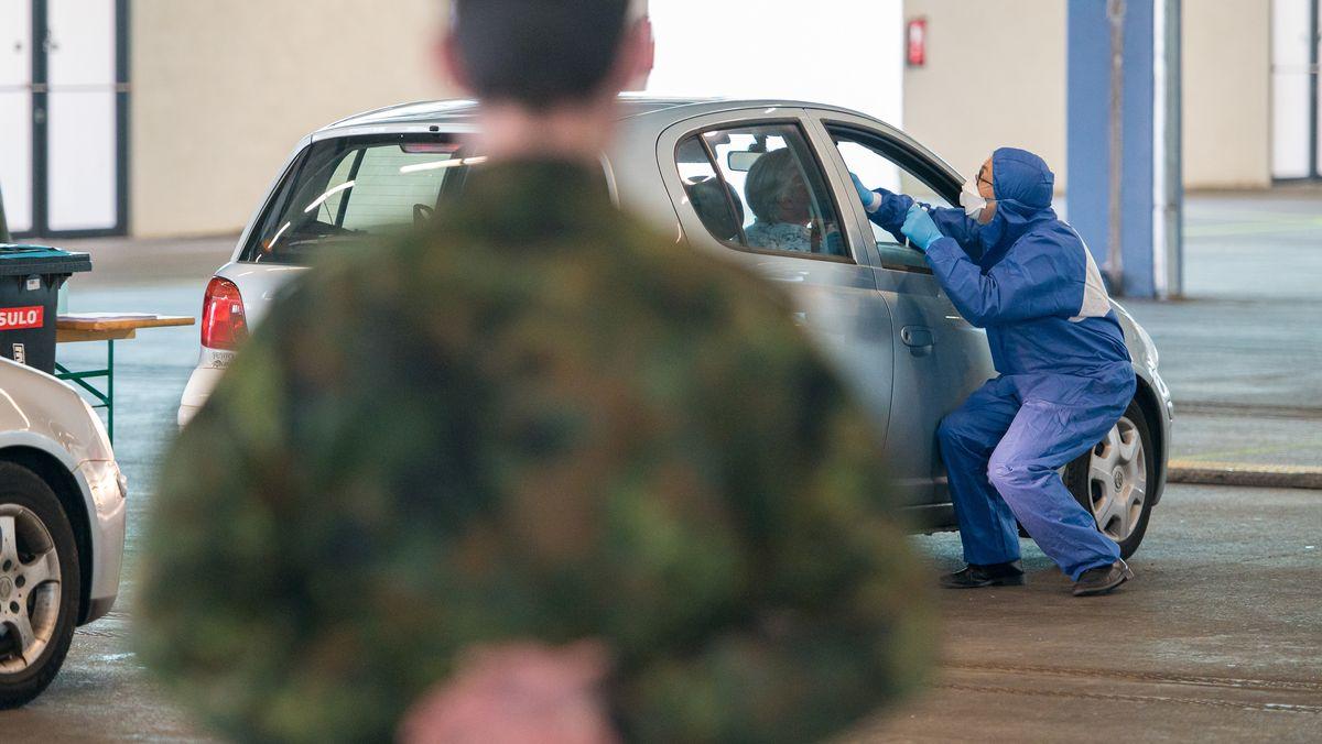 Ein Arzt nimmt bei der von der Bundeswehr organisierten Drive-in-Teststation in Saarbrücken einen Abstrich.