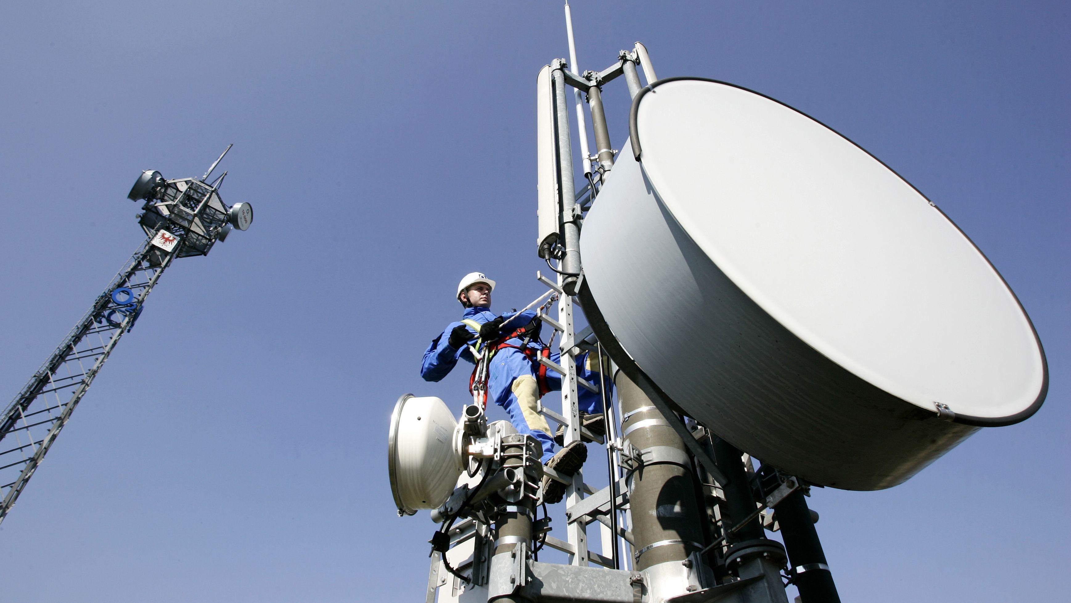 Techniker bei Wartungsarbeiten an Mobilfunkmasten mit Richtantennen für den Empfang von Handy-Funkverkehr