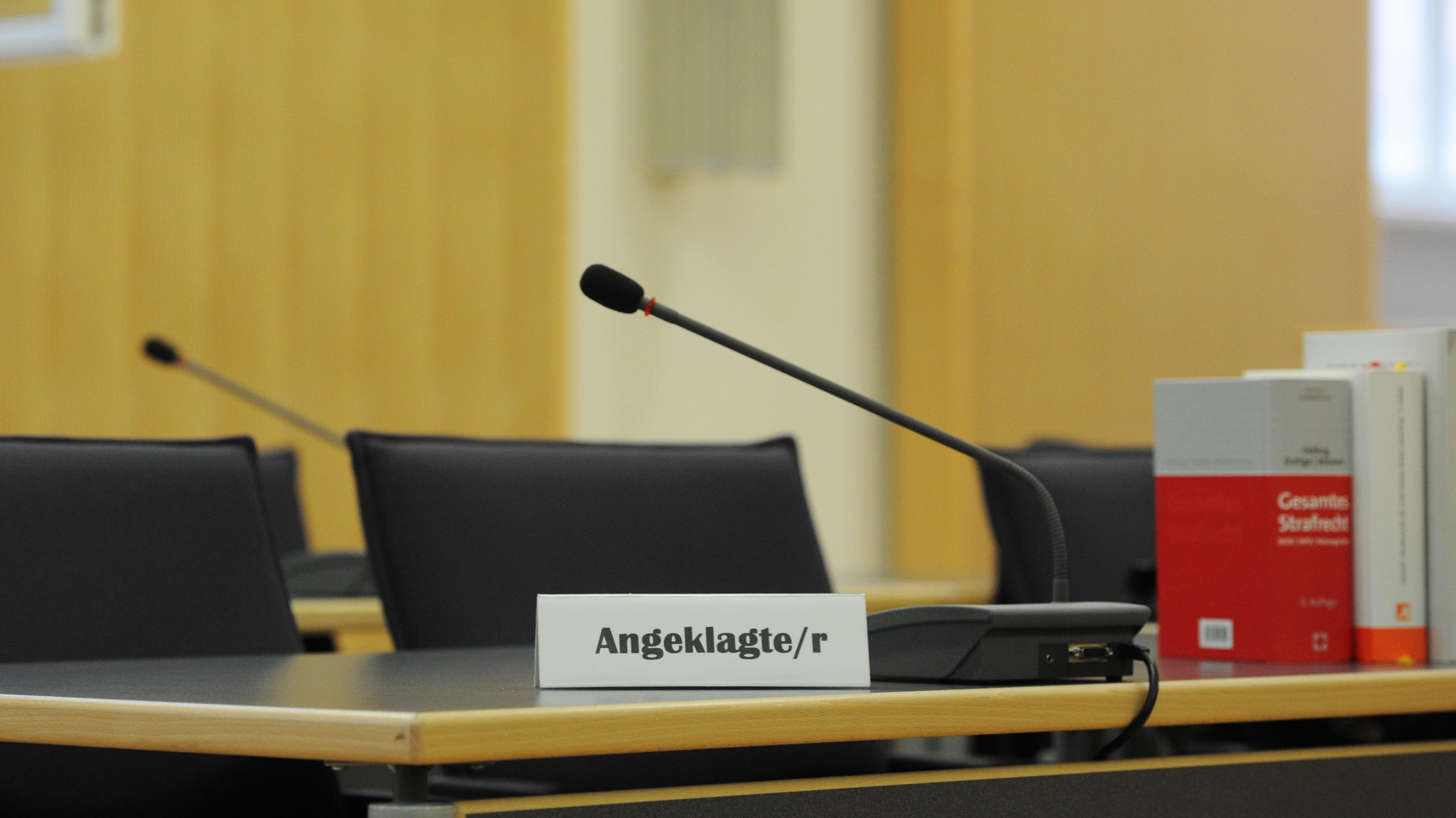 """Ein Schild mit der Aufschrift """"Angeklagte/r"""" steht im Gerichtssaal im Landgericht in Regensburg."""