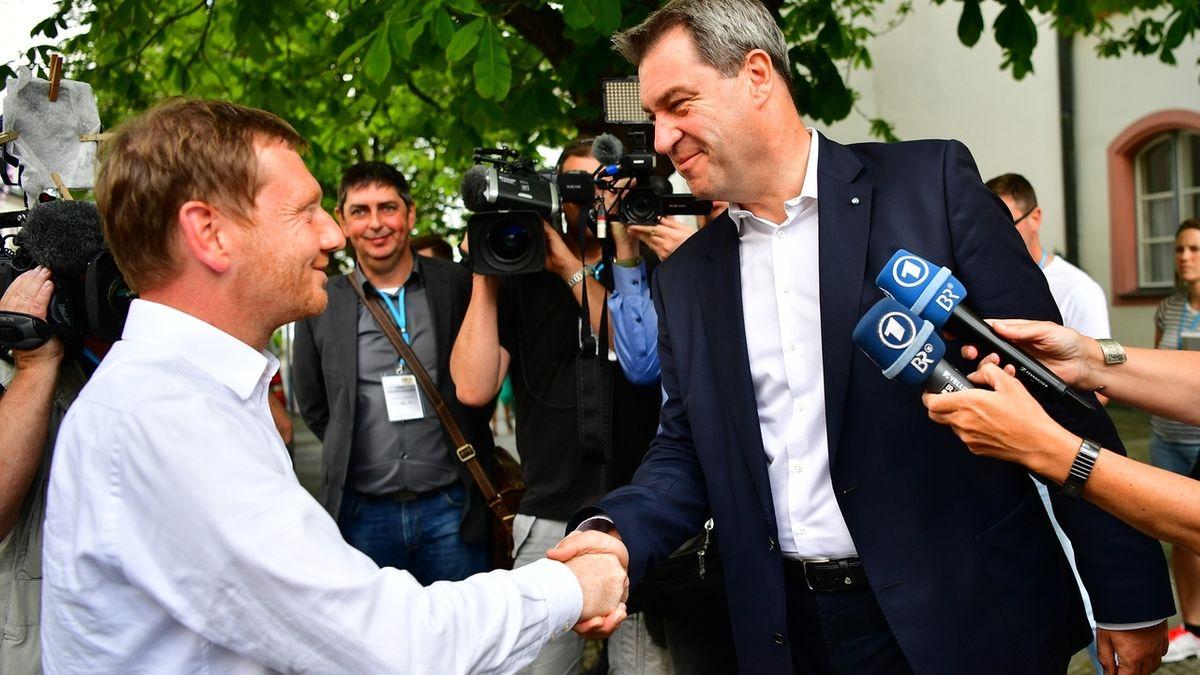 Sachsens Ministerpräsident Michael Kretschmer (links) gibt dem bayerischen Ministerpräsidenten Markus Söder am Rande einer gemeinsamen Kabinettssitzung 2018 in Hof die Hand.