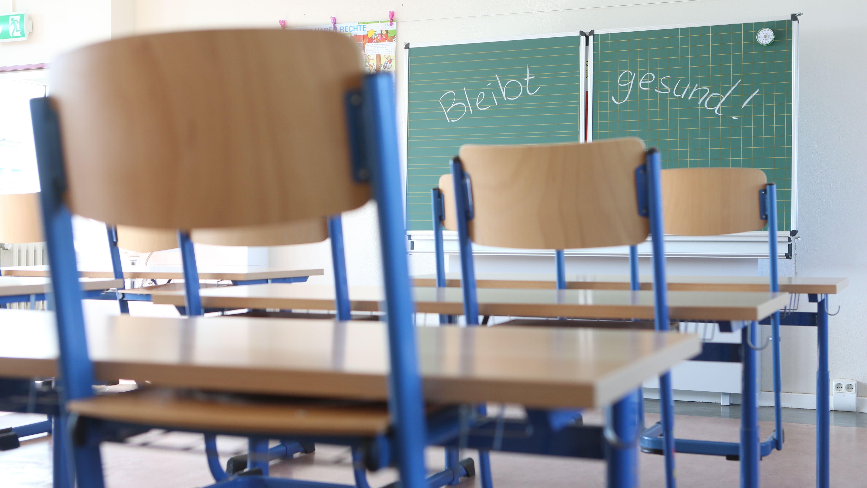 """Leeres Klassenzimmer, an der Tafel steht """"Bleibt gesund!"""""""
