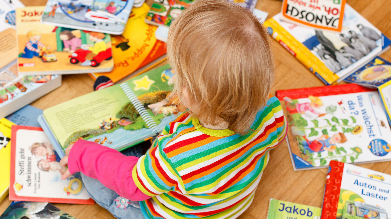 Ein Kind sitzt mit vielen Kinderbüchern auf dem Boden