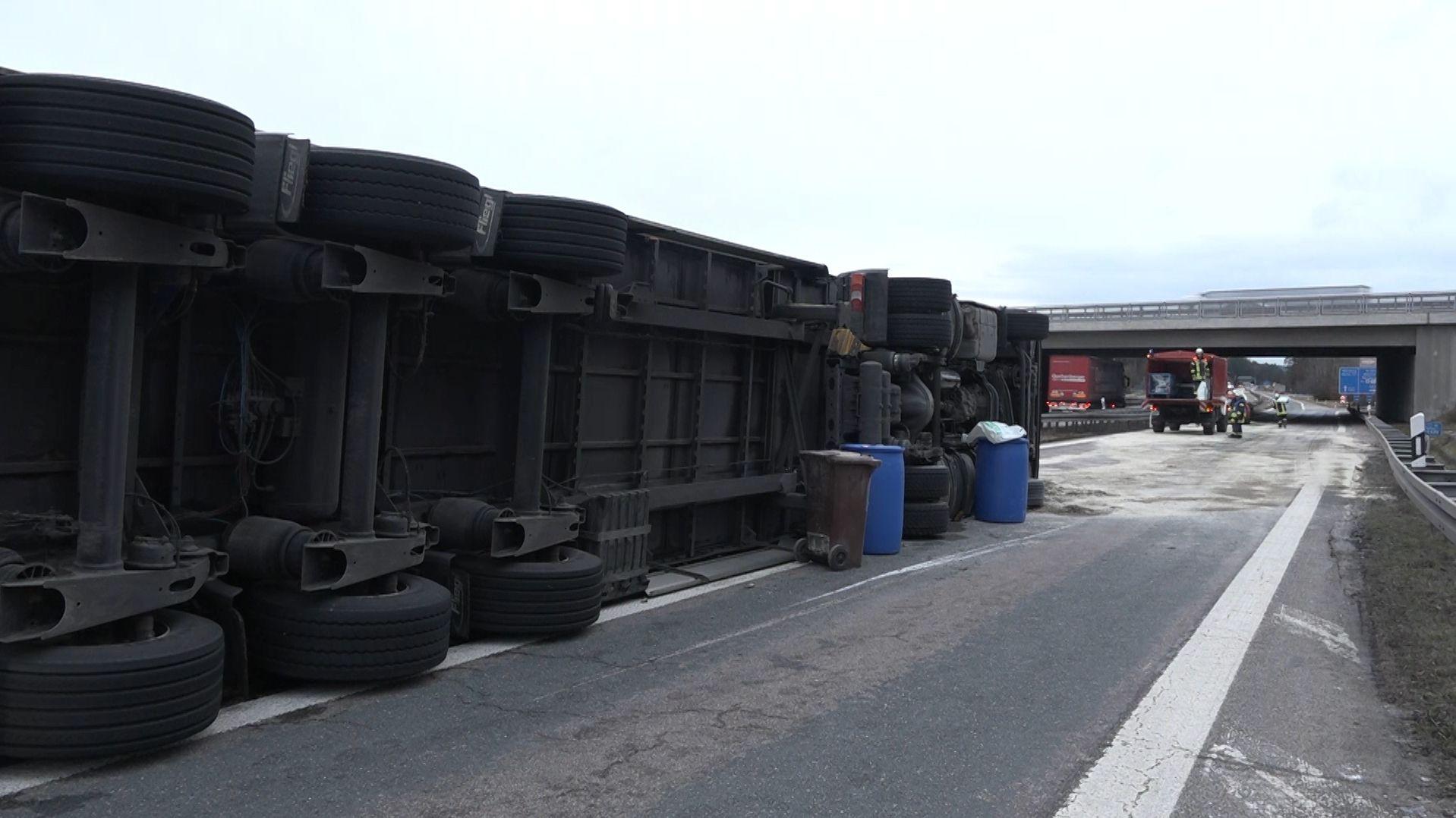 Ein Lkw liegt seitlich auf der Autobahn.