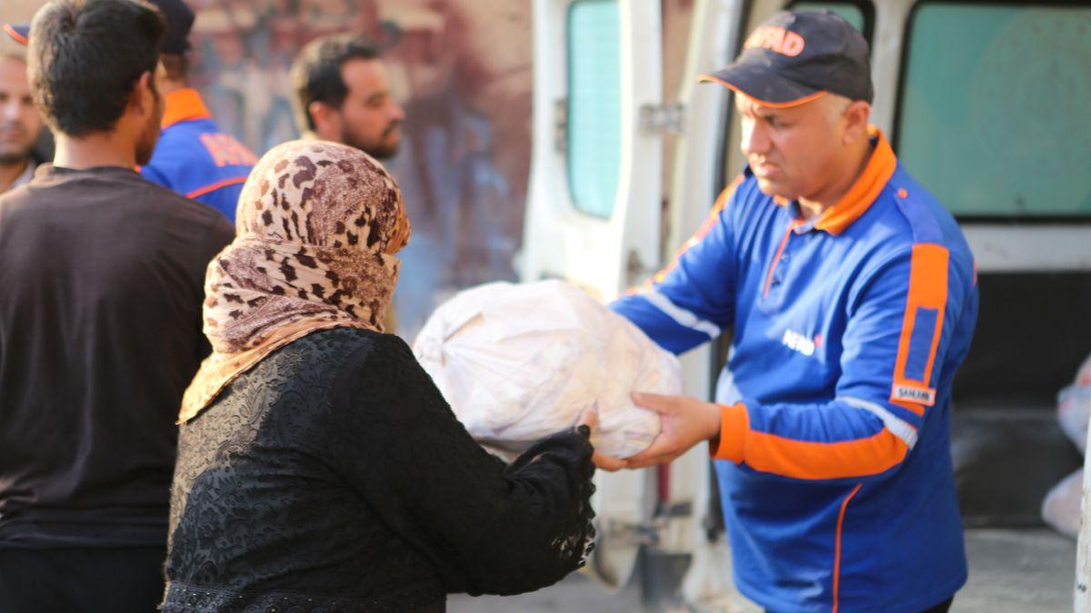 Mann gibt Brot-Paket an Frau weiter.