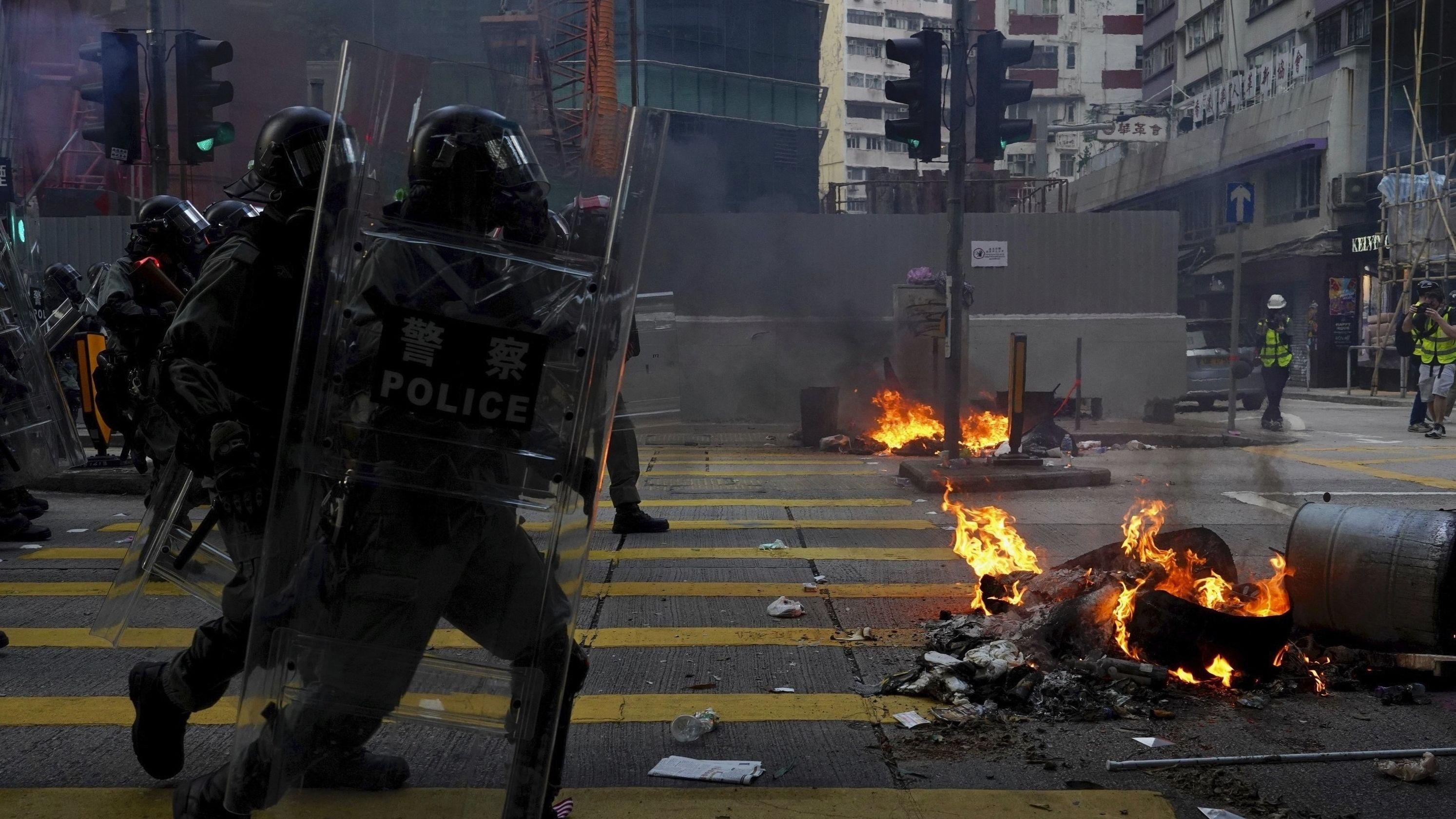Polizisten in Hongkong während einer Demonstration am 1. Oktober 2019. Die Polizisten tragen Schutzkleidung und befinden sich nahe einer brennenden Barrikade.