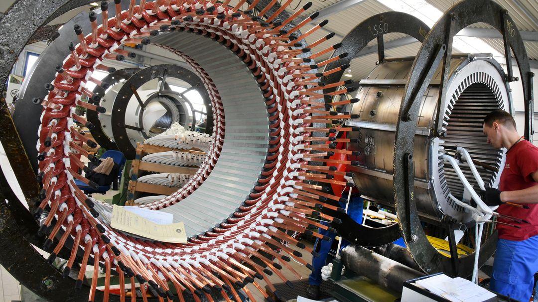 In einem Reparaturwerk arbeitet ein Mitarbeiter an Statoren für Elektromotoren und Generatoren