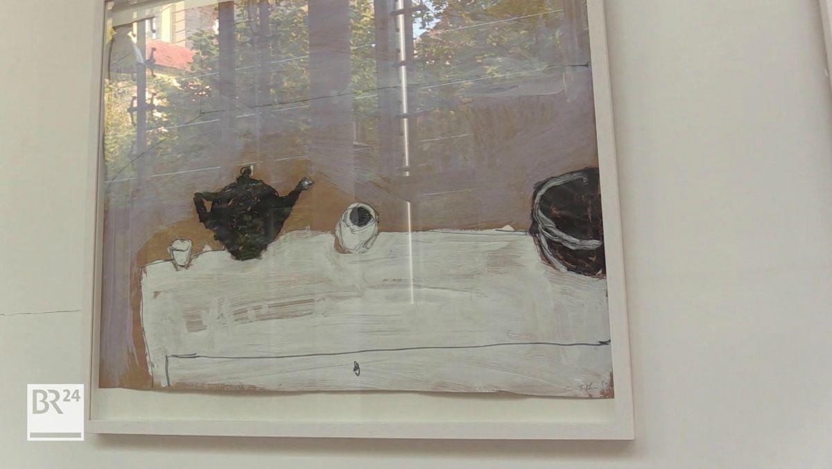 Auf einem Bild ist eine schwarze Kaffeekanne zu sehen, daneben zwei Trinkbecher.