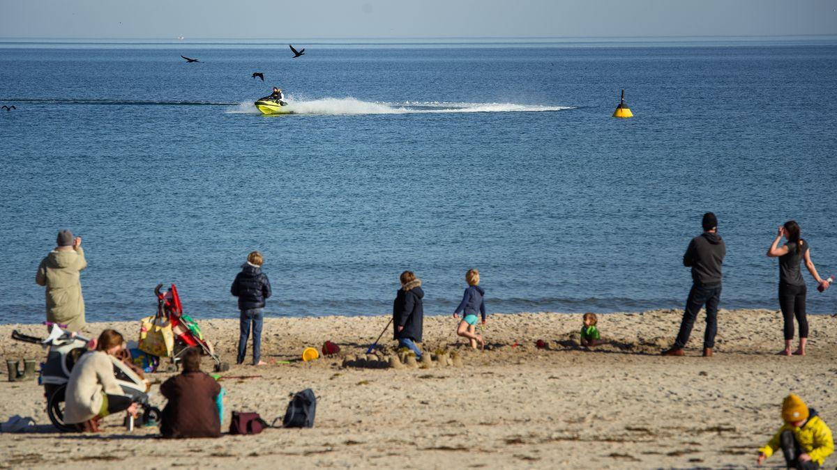 Ausflügler beobachten bei frühlingshaften Temperaturen am Timmendorfer Strand in der Lübecker Bucht einen Jet-Ski