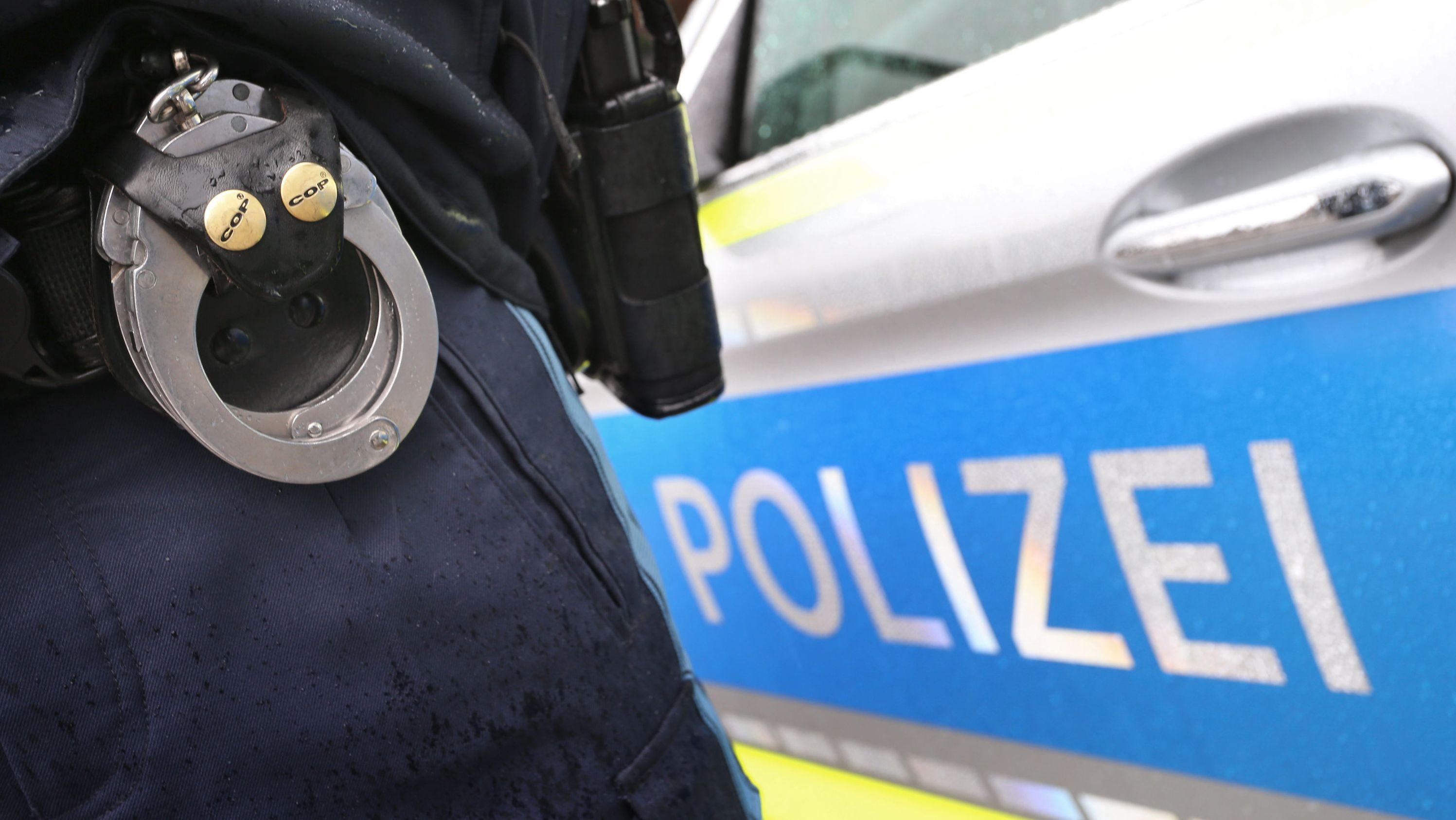 Symbolbild: Handschellen und Polizeiauto