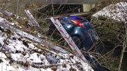 Ein Auto wird mit Leitern aus einem Bach geborgen.   Bild:News5