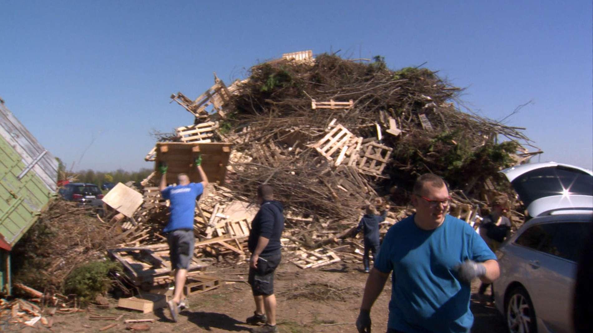 Männer schichten Holz auf für das Osterfeuer