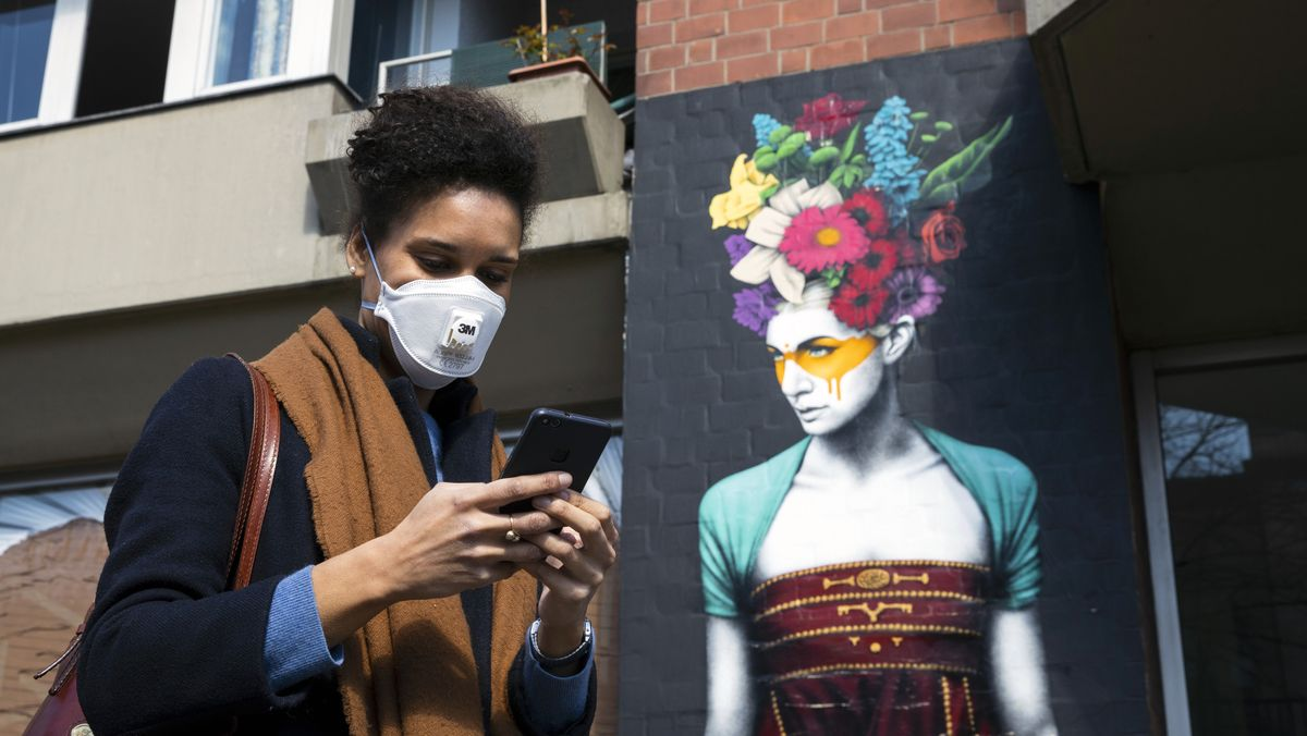 Woman using her smartphone while wearing a face mask