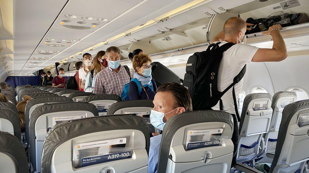 Passagiere mit Mund-Nasen-Schutz an Bord eines Flugzeugs (Archivbild)
