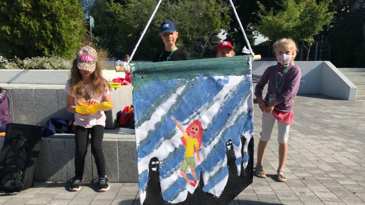 Vier Grundschulkinder zeigen einen selbst gestalteten Wimpel