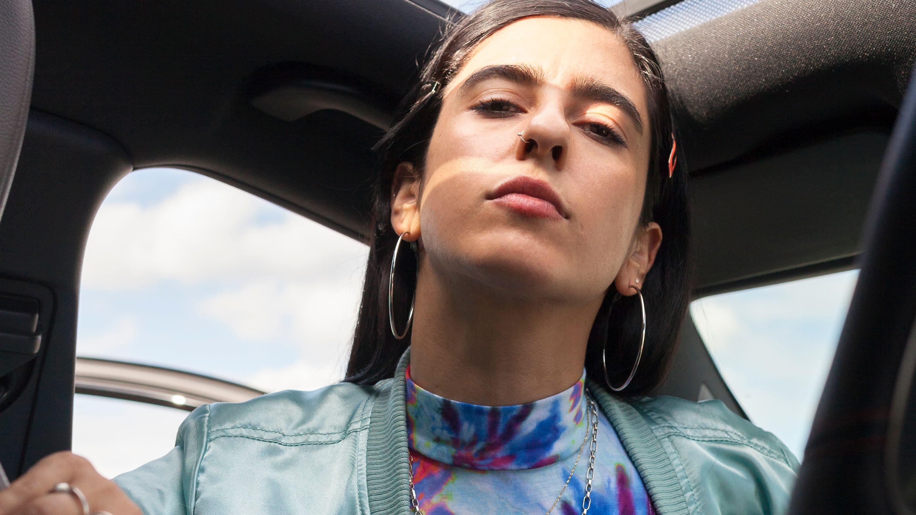 Autorin und Künstlerin Cemile Sahin blickt aus einem offenen Auto von oben herab in die Kamera