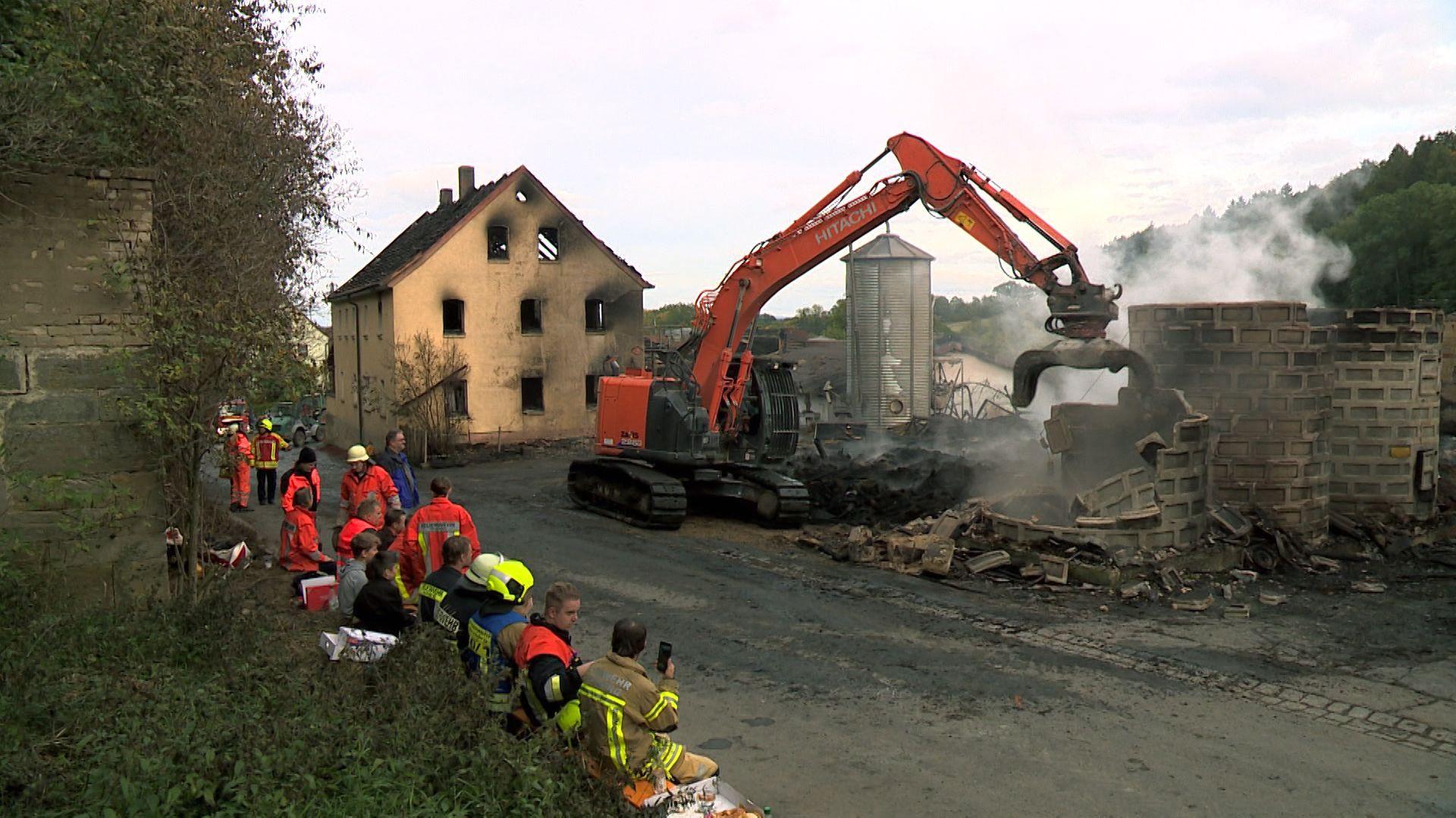 Helfer stehen vor den Ruinen des abgebrannten Bauernhofs, ein Bagger schaufelt Schutt.