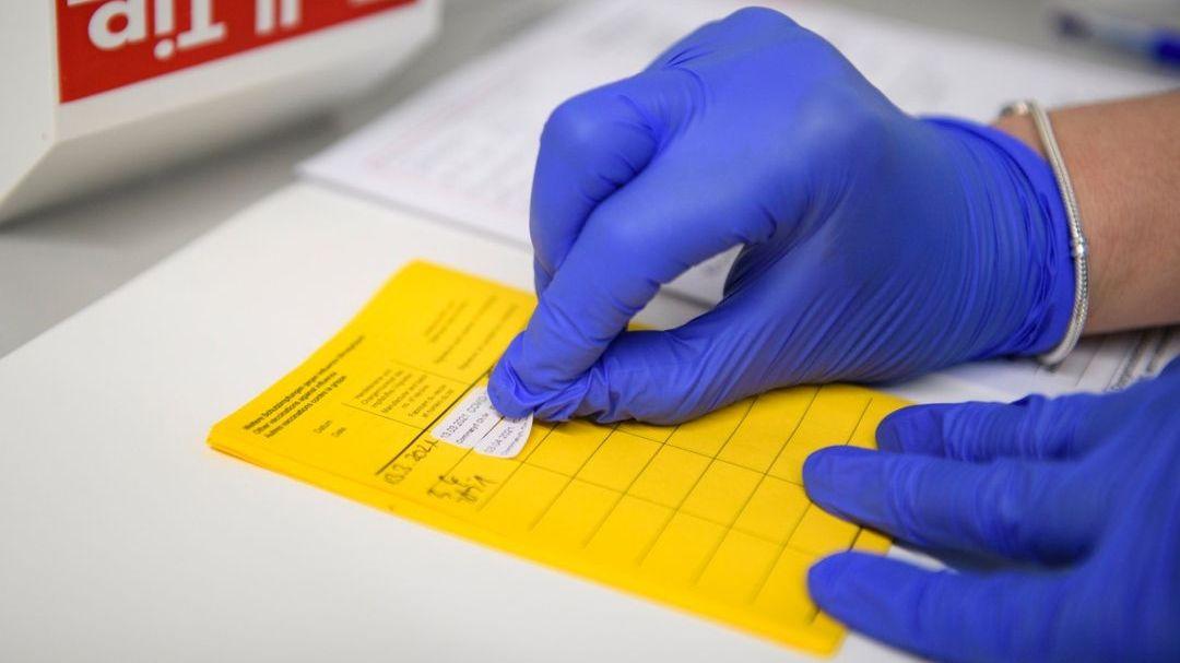 Aufkleber wird in gelben Impfpass geklebt.