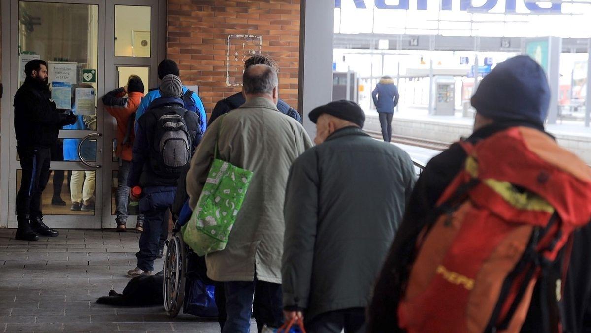 Eine lange Schlange vor der Münchner Bahnhofsmission an Gleis 11. Durch eine kleine Klappe bekommen sie Essen, Trinken und Kleidung.