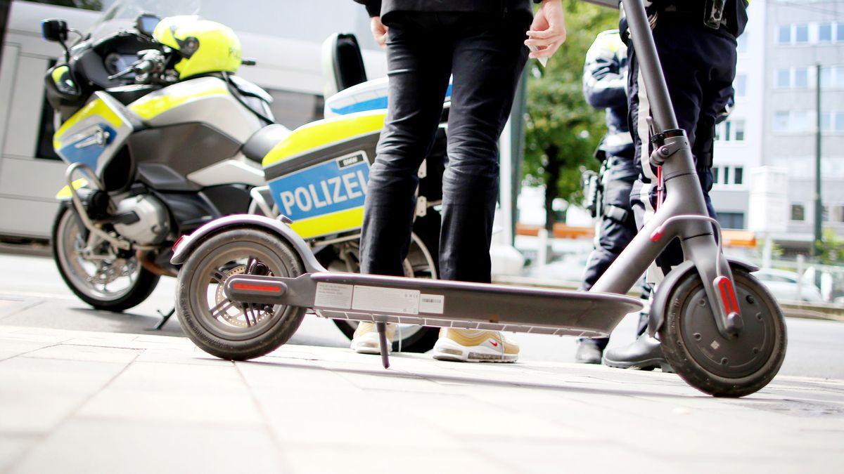 Polizisten kontrollieren einen E-Scooter-Fahrer