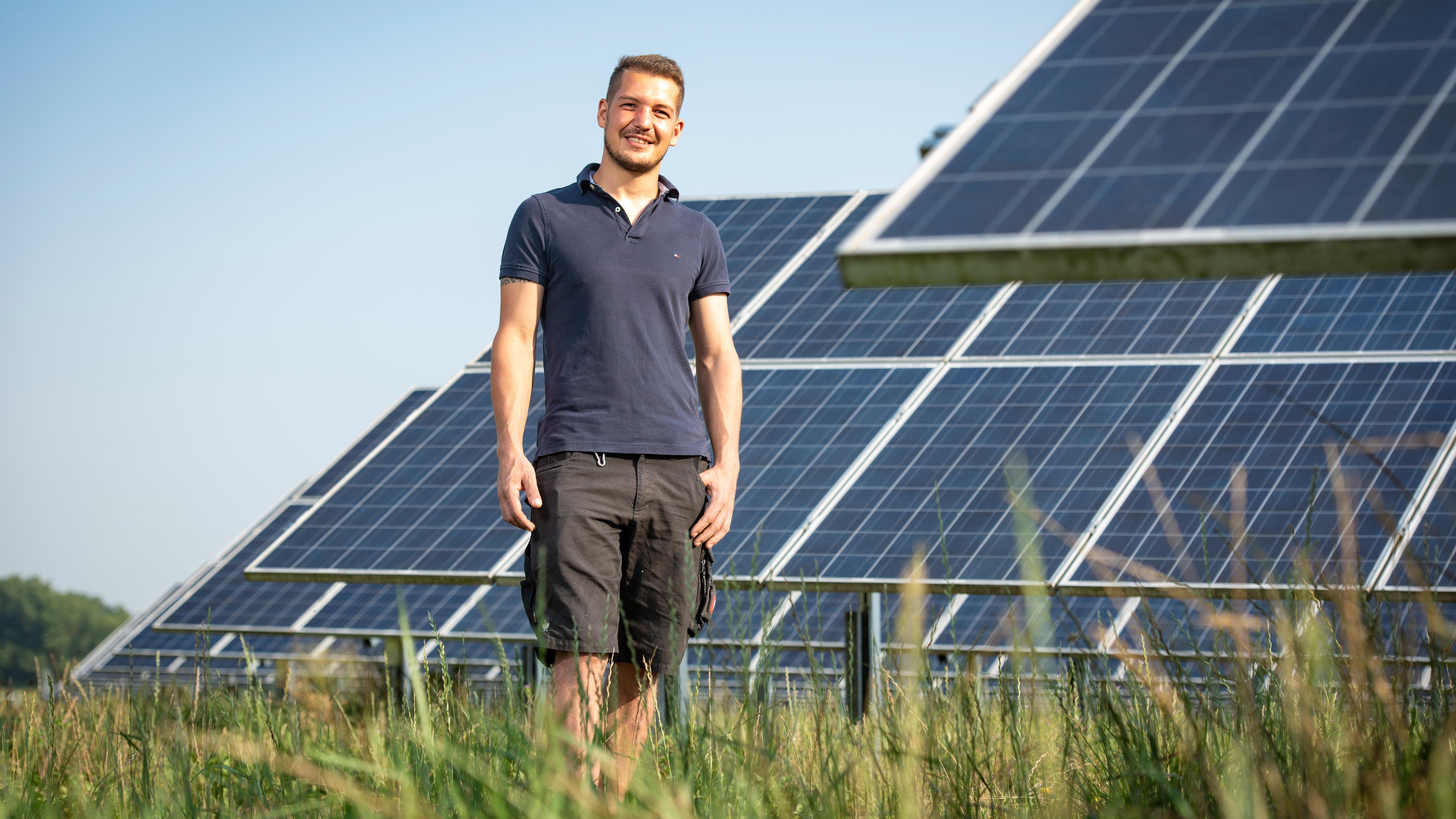 Alois Stefan Penninger auf einer Wiese vor Solaranlagen