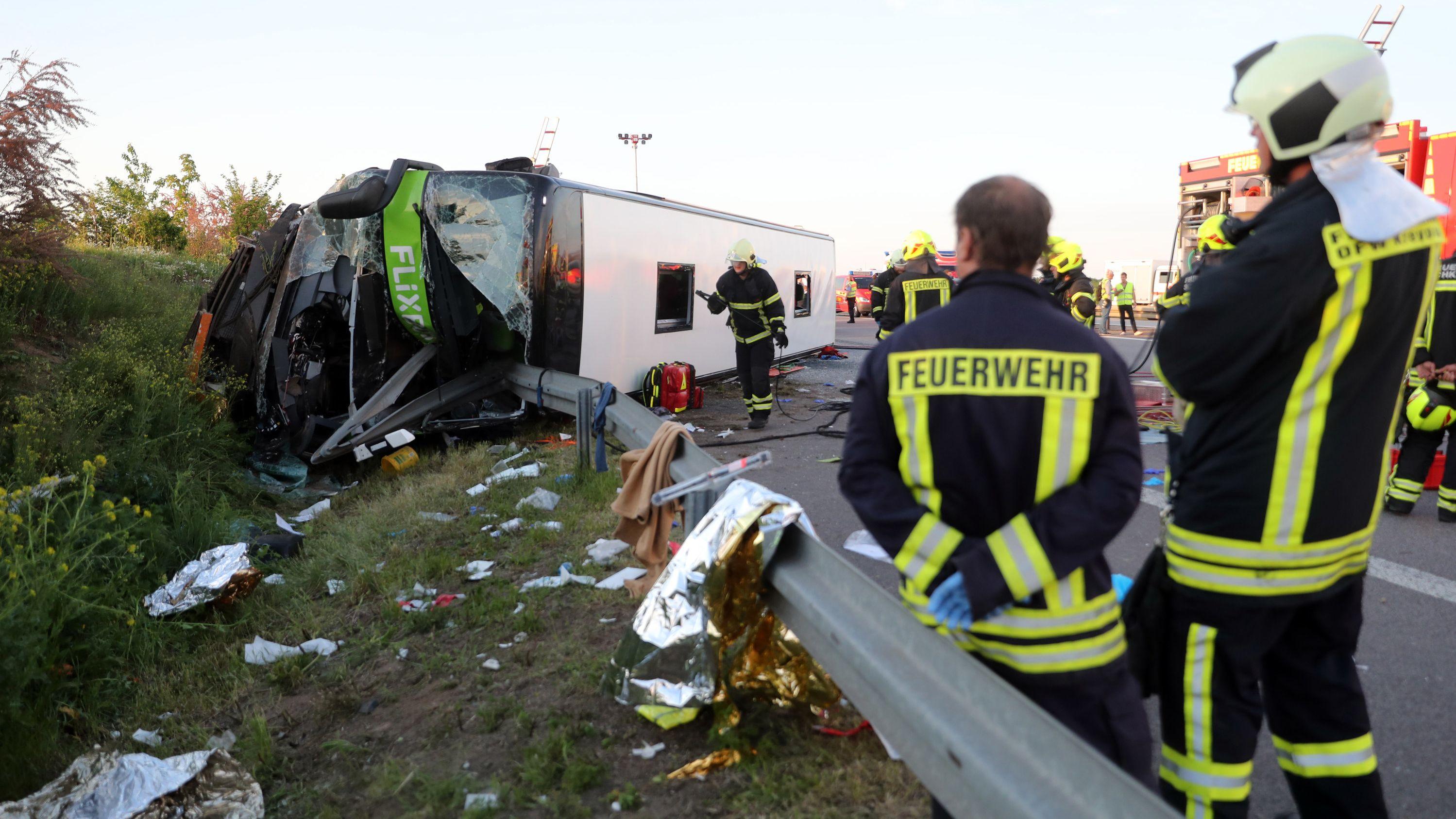 Archivbild: Am 19.05.2019 auf der A9 bei Leipzig: Einsatzkräfte der Feuerwehr stehen an der Unfallstelle neben dem verunglückten Bus.