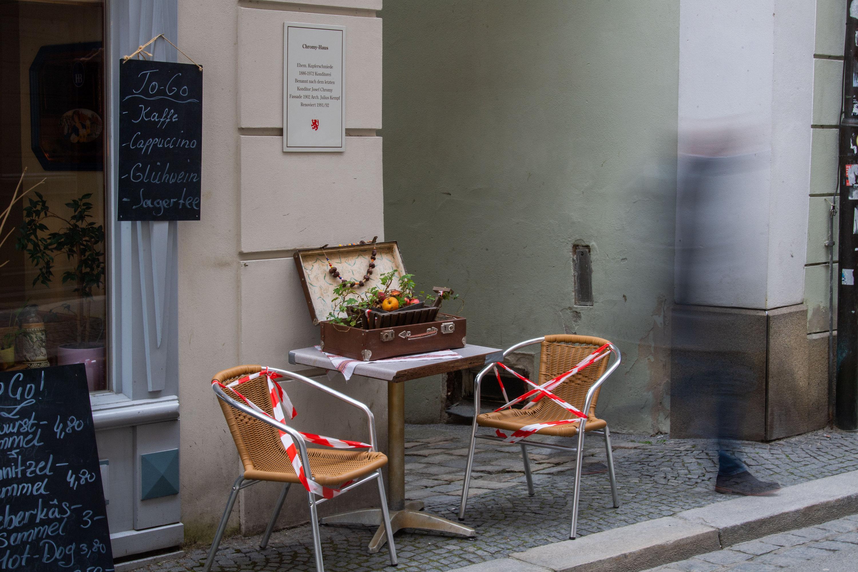 Ein Mann geht an Stühlen eines Cafés vorbei, die mit Flatterband gesperrt wurden.