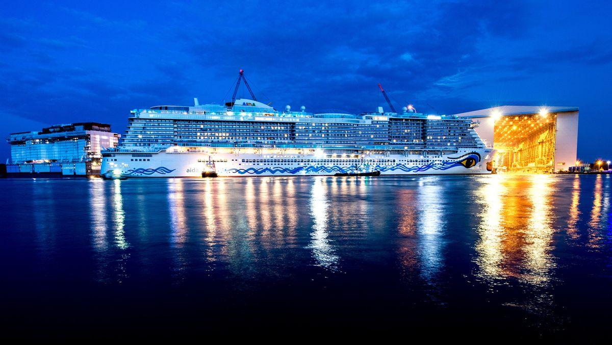 Schlepper ziehen im Jahr 2018 das neue Kreuzfahrtschiff Aidanova aus der überdachten Werfthalle der Meyer-Werft