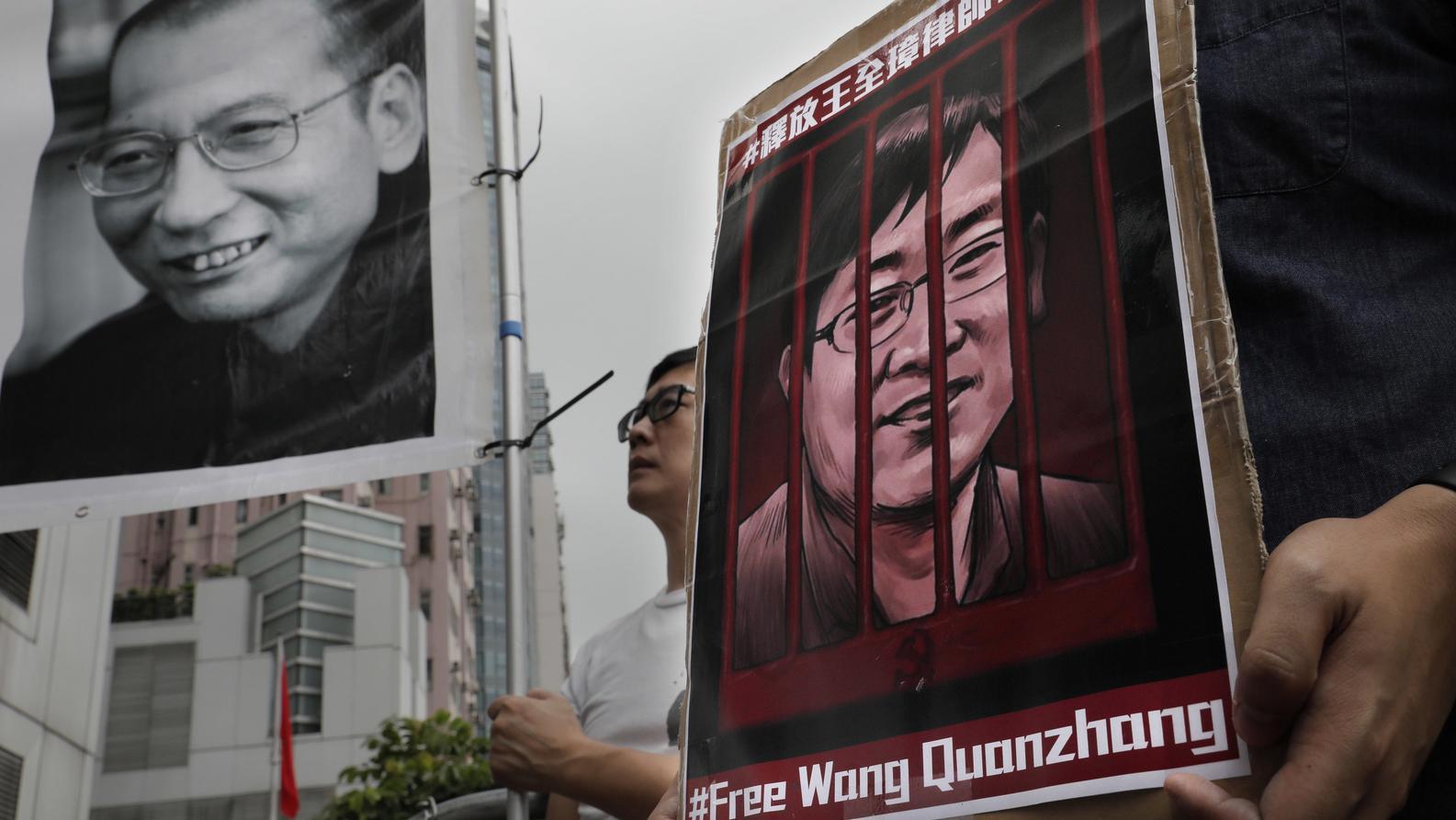 China, Hongkong: Demonstranten halten Plakate mit dem Bild des gestorbenen chinesischen Friedensnobelpreisträgers Liu Xiaobo (l) und des inhaftierten Menschenrechtlers Wang Quanzhang während einer Protestkundgebung.
