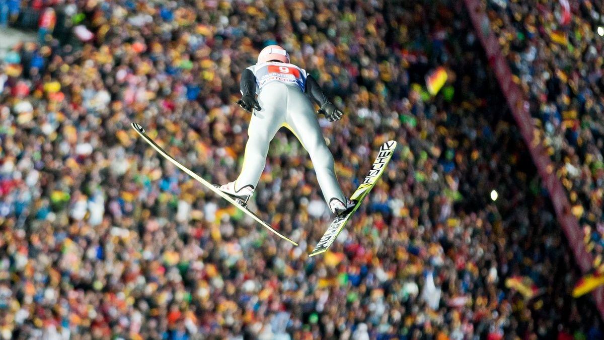 Ein Sportler schwebt von der Schanze auf ein Zuschauer-Meer in der Skisprungarena zu