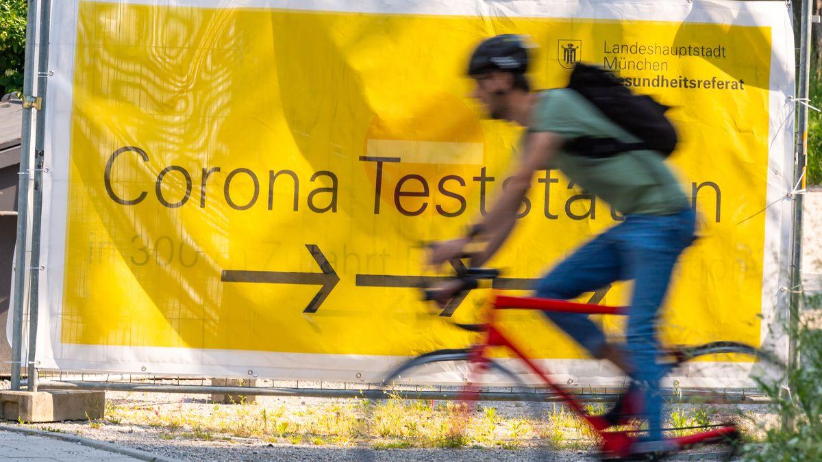 Ein Radfahrer fährt an einem Schild für eine Corona-Teststation vorbei.