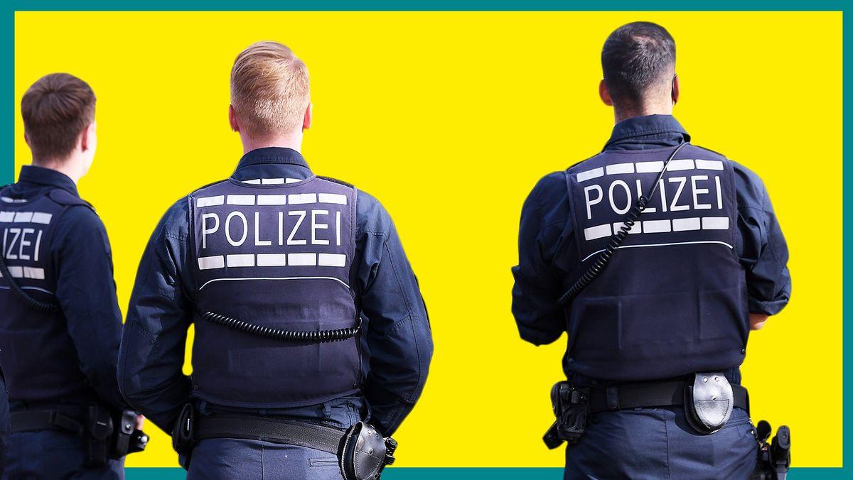 Drei Polizisten in Uniform und mit Schutzweste.