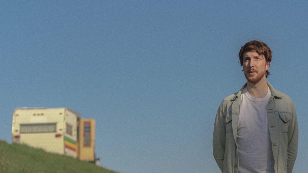 Aidan Knight steht im Sommer im Freien, die Hände am Rücken. Im Hintergrund ist ein Wohnmobil zu sehen.