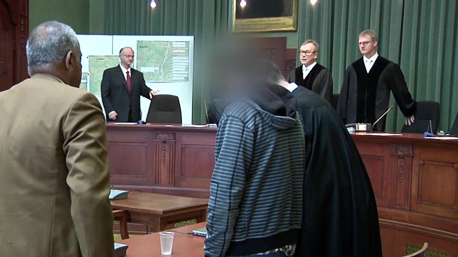 Der wegen Mordes angeklagte Lkw-Fahrer im Landgericht Bayreuth, im Hintergrund die Richter.