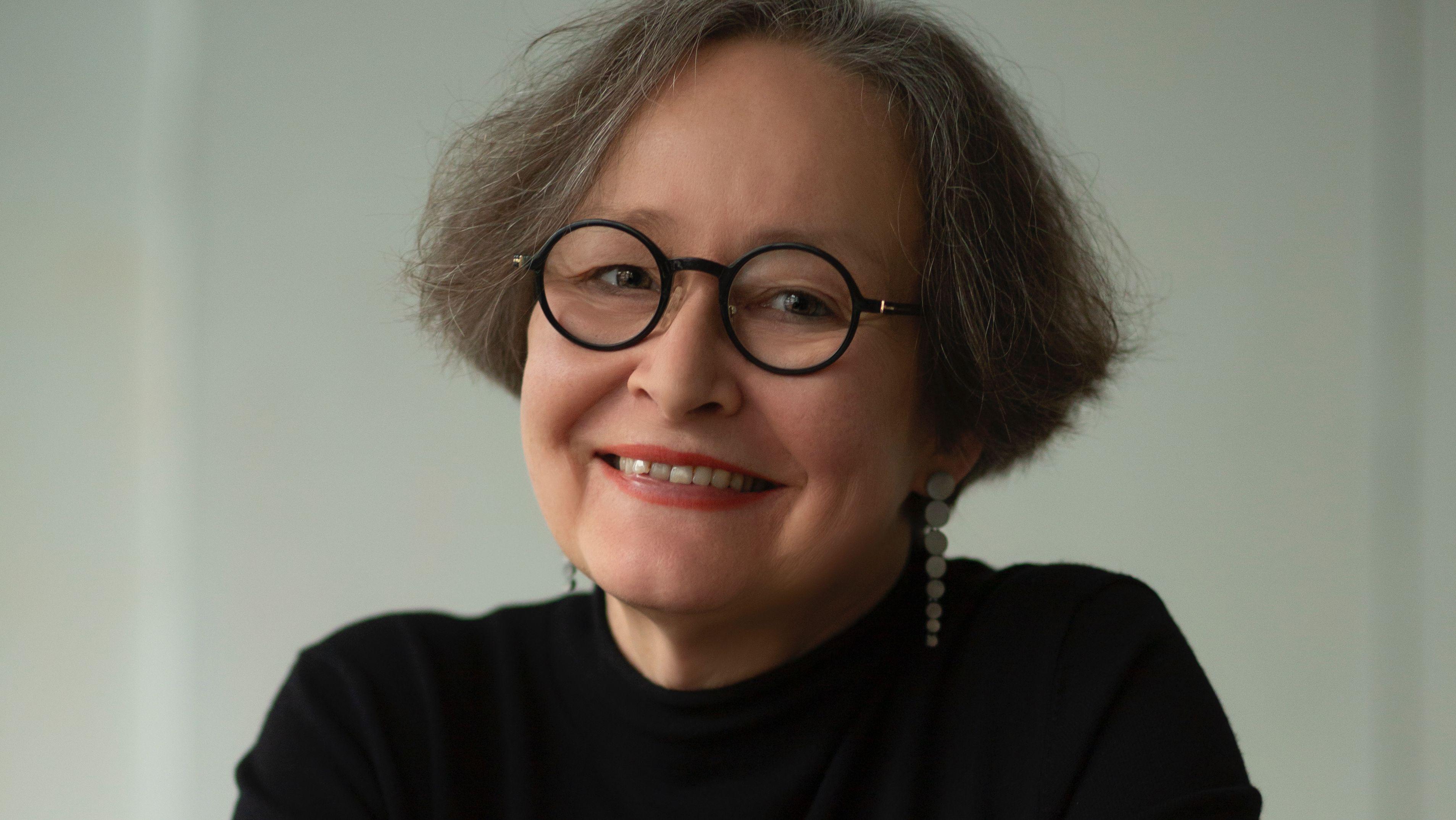 Ein Porträt der Schmuckgestalterin Alexandra Bahlmann, mit braunem Kurzhaarschnitt, markanter schwarz gerahmter Brille und Hängeohrringen