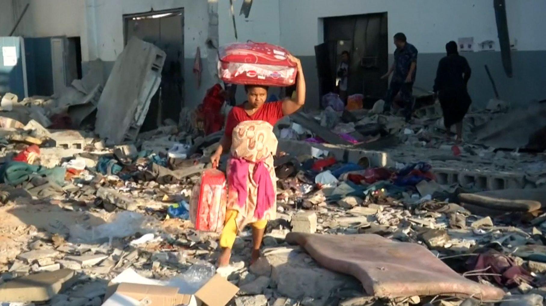 Eine Frau trägt ihre Habe aus den Trümmern des Lagers