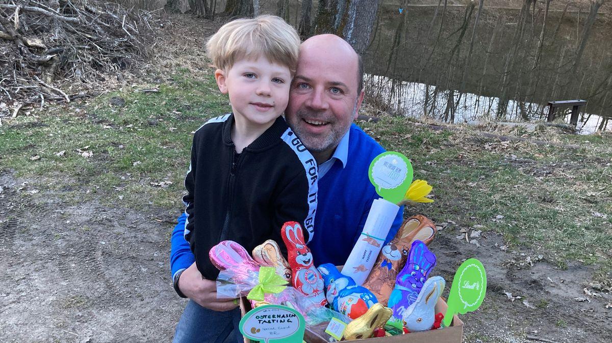 Karsten Riedel und sein Sohn Ben, sechs Jahre, halten eine  Pappkiste mit 10 Schokoosterhasen  in den Händen.