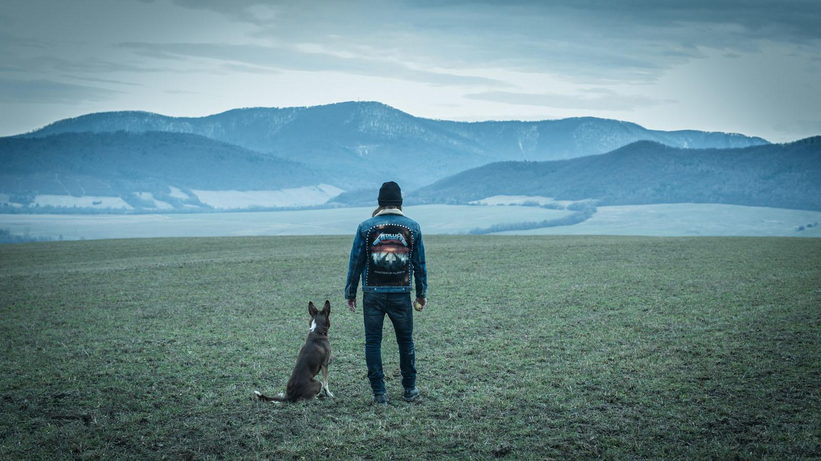 Von hinten sieht man in der hügeligen Landschaft Westpolens einen Mann und seinen  Hund.