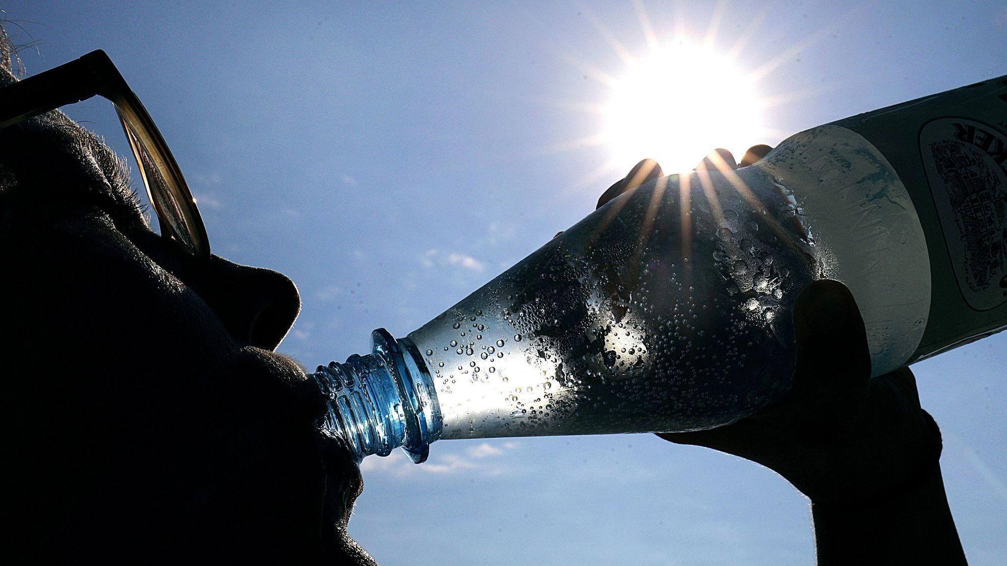 Eine Frau mit Sonnenbrille trinkt bei Sonnenschein aus einer Flasche Wasser.
