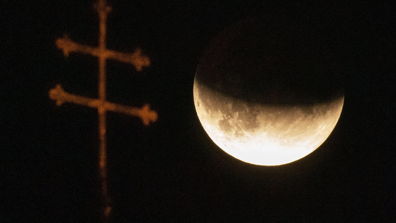 Der Mond ist während einer partiellen Mondfinsternis hinter einem Kreuz auf dem Dach der Heiliggeistkirche in München zu sehen.