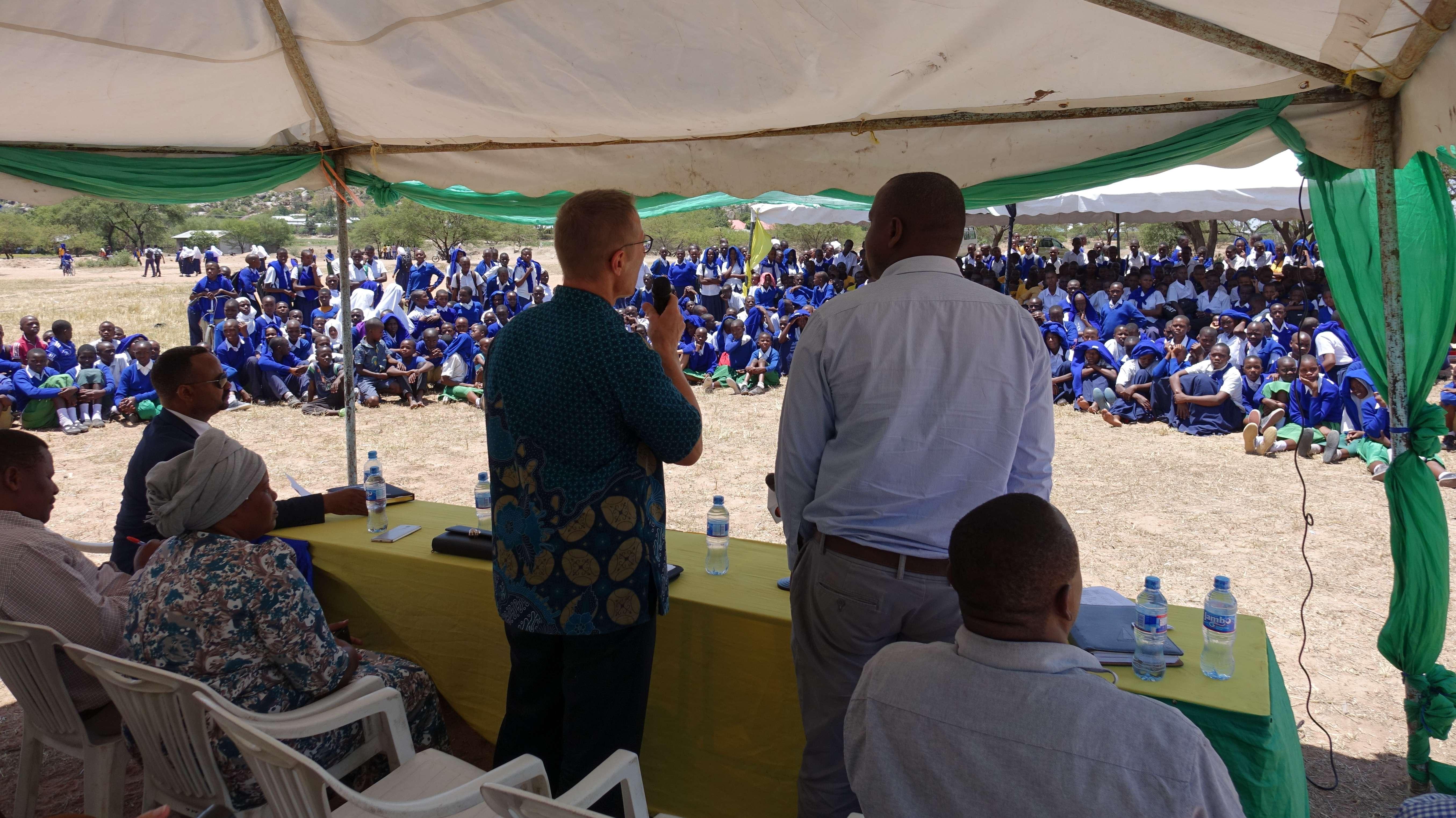 Dr. Andreas Müller erläutert Schülern und Multiplikatoren im Distrikt Magu die Hintergründe des Projekts zur Bekämpfung der Schistosomiasis . Zusätzlich anwesend sind weitere politische Ehrengäste aus der Stadt Mwanza und dem Distrikt Magu, sowie der medizinischen Direktor des Distrikts.