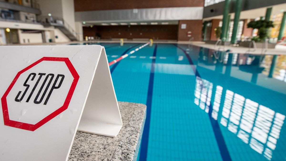 """Stop"""" steht auf einem Schild auf einem gesperrten Startblock am Beckenrand eines Schwimnbades. In ganz Deutschland hat ein vierwöchiger Teil-Lockdown begonnen, um die Ausbreitung des Coronavirus zu bremsen."""