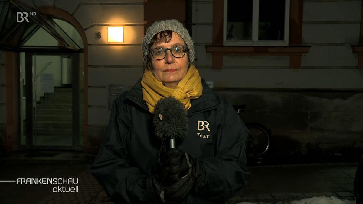 BR-Reporterin Annerose Zuber mit grauer Strickmütze und gelbem Schal steht mit Mikrophon vor dem Gesundheitsamt in Hof und berichtet live für das Fernsehen.