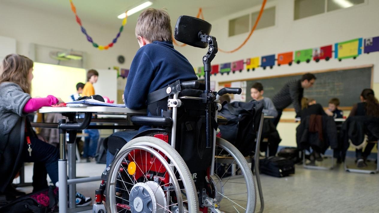 Bub im Rollstuhl zusammen mit anderen Kinder in einer Klasse