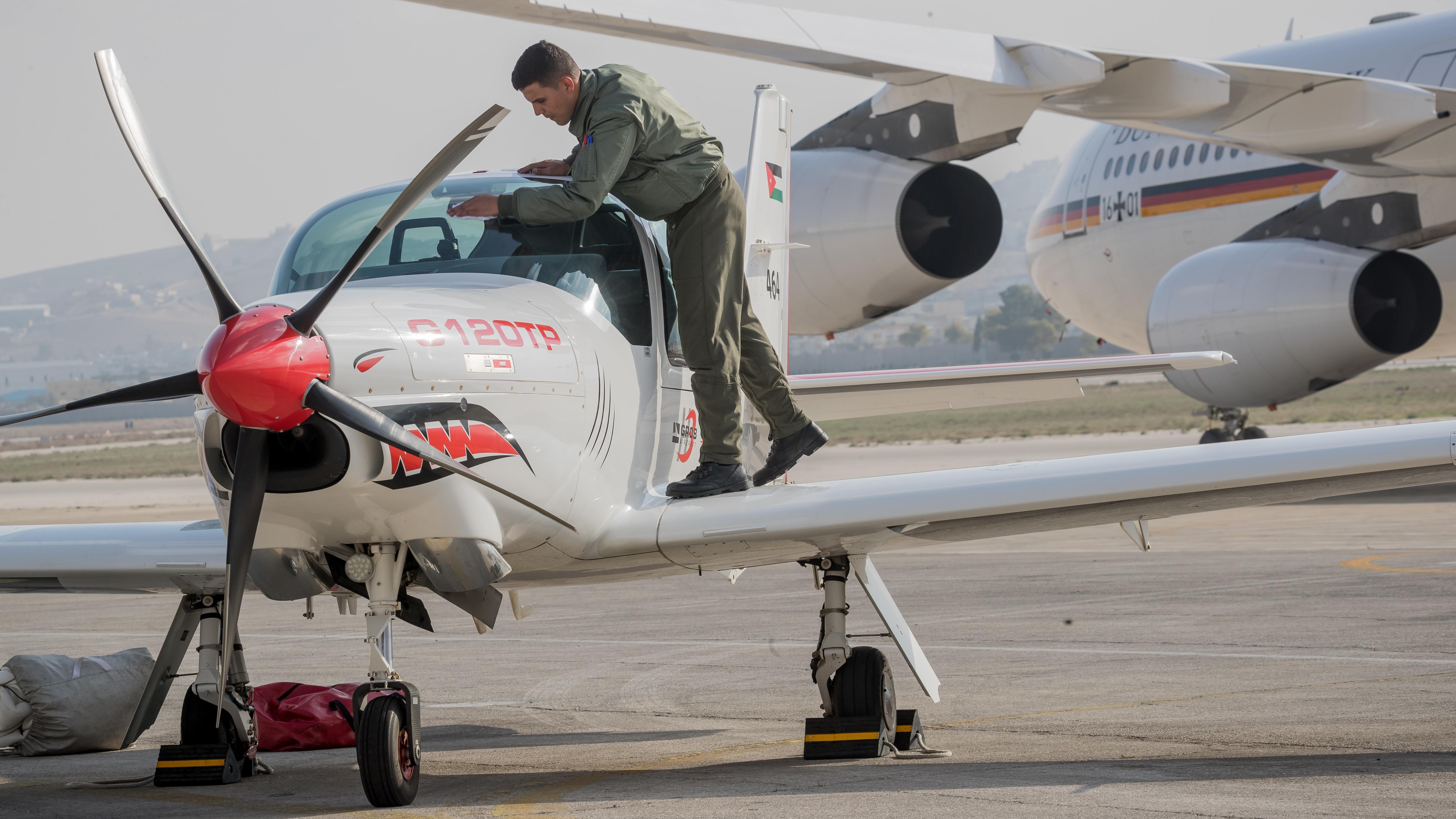 Ein Trainingsflugzeug vom Typ Grob G120TP steht auf der Luftwaffenbasis Marka IAP in Amman in Jordanien. Auf einem Flügel steht ein Mann