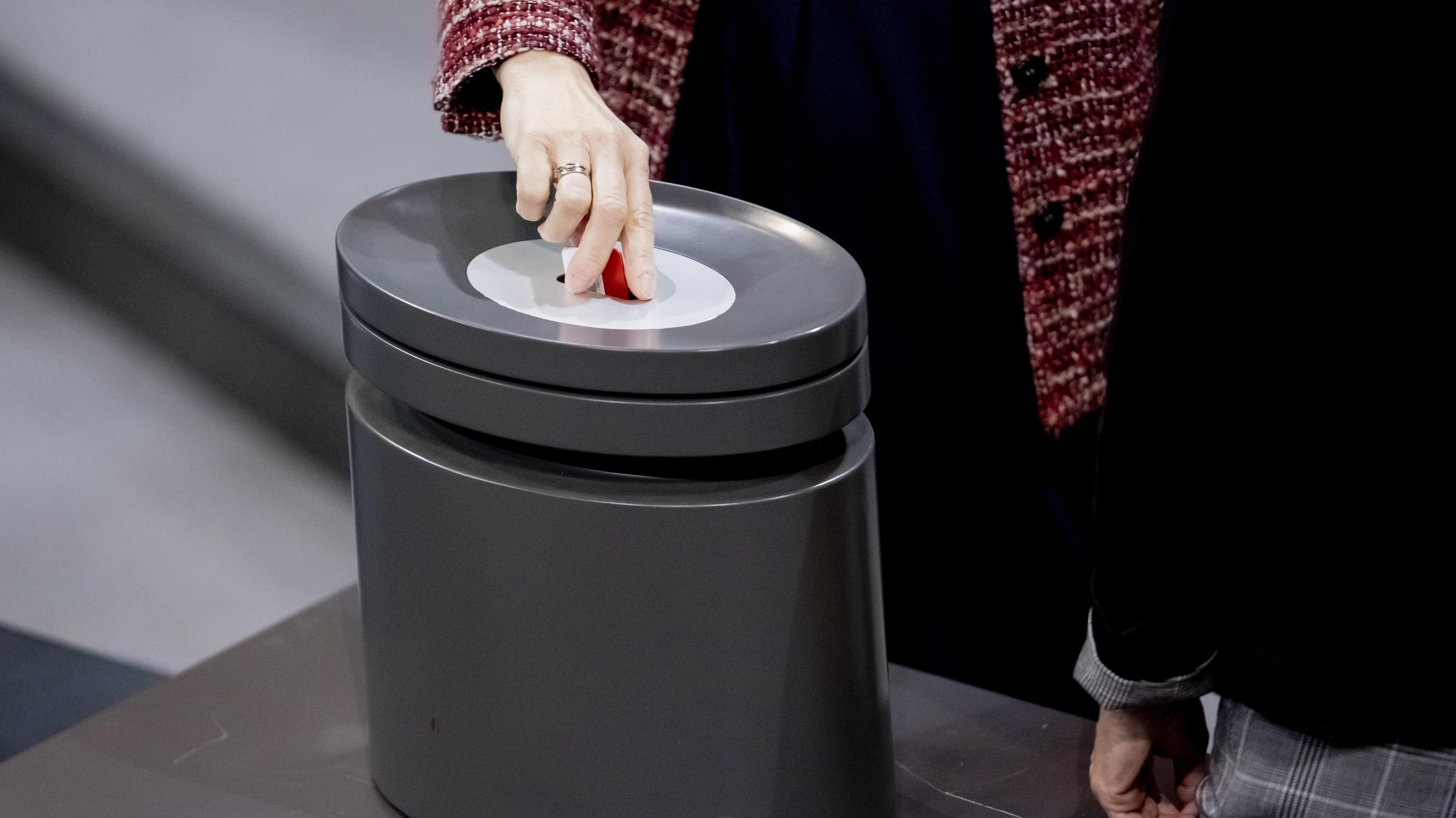 Eine Bundestagsabgeordnete steckt bei einer Abstimmung im Deutschen Bundestag ihre Stimmkarte in eine Wahlurne
