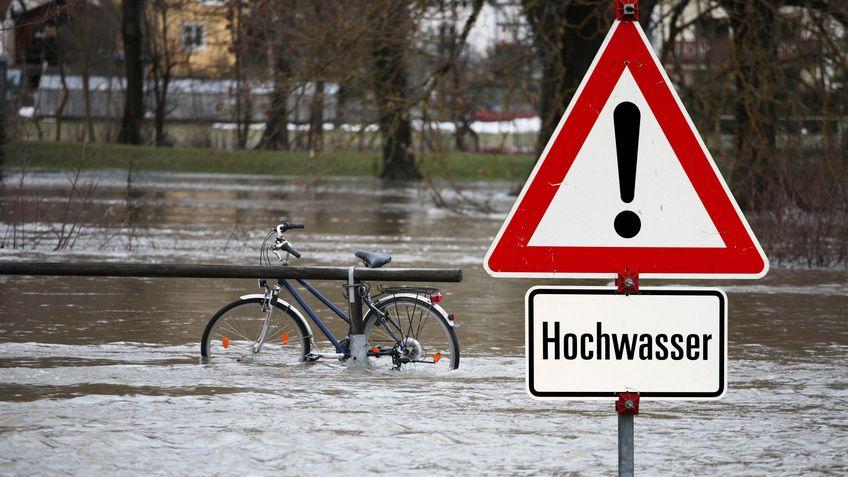 """Ein Schild auf dem """"Hochwasser"""" steht. Im Hintergrund ist Hochwasser zu sehen."""
