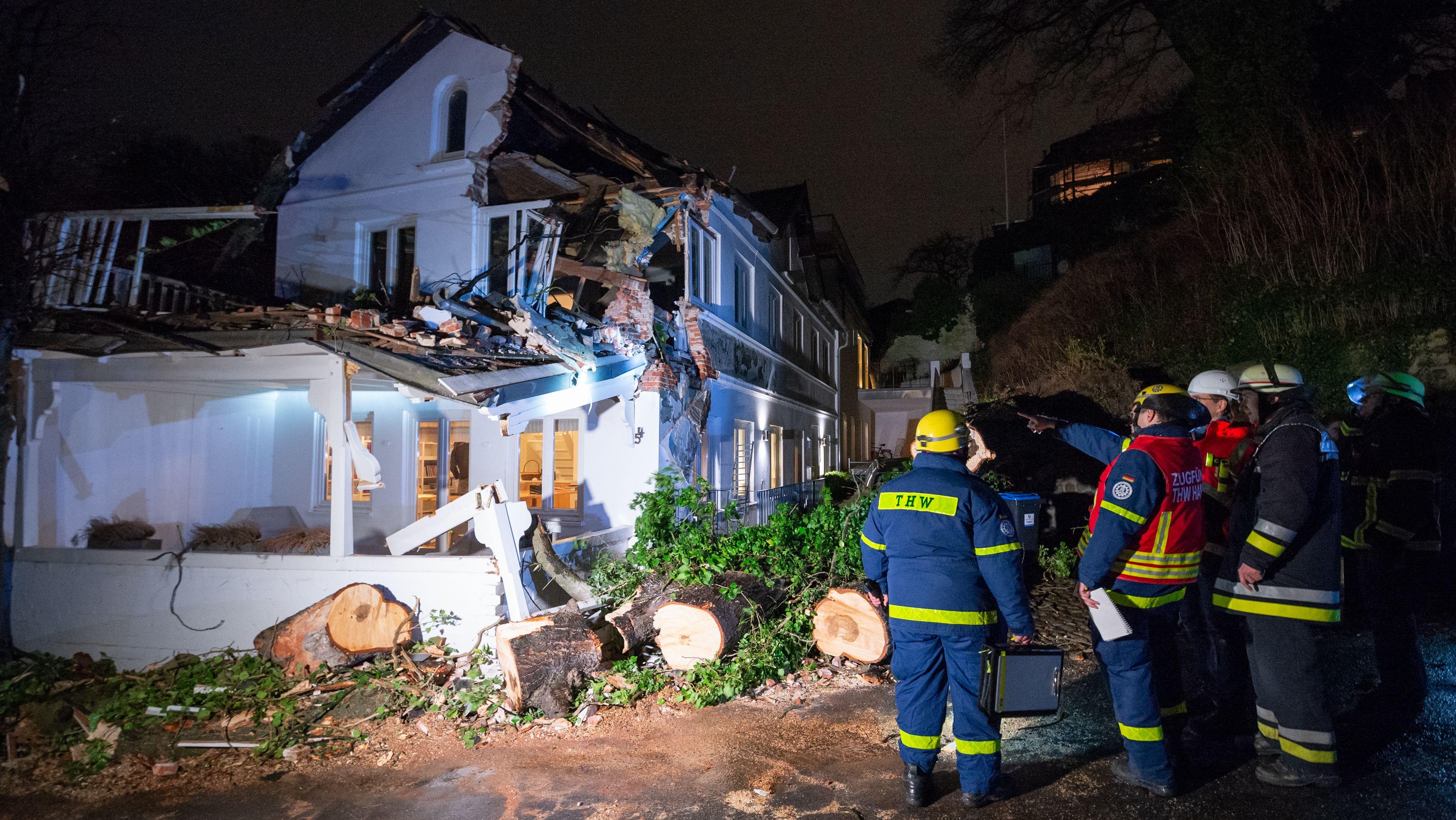 Einsatzkräfte des Technischen Hilfswerks stehen in Hamburg an einem Wohnhaus, das durch einen umgekippten Baum stark beschädigt wurde.